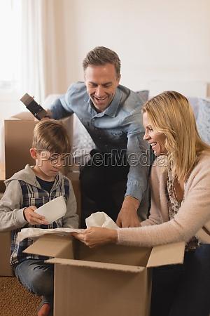 familie packt kartons in ihrem neuen