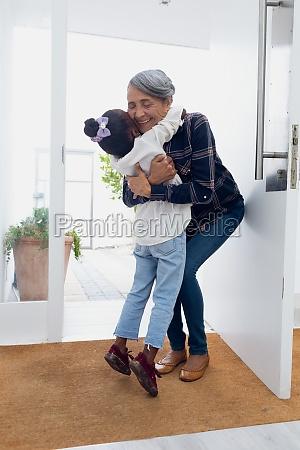 maedchen umarmt grossmutter an der tuer