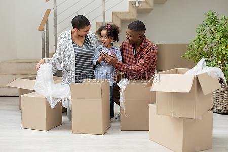 familie packt kartons im wohnzimmer aus