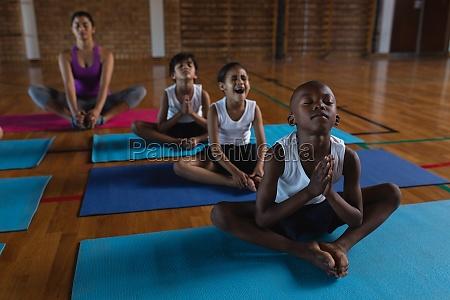 yogalehrerin und schulkinder beim yoga und