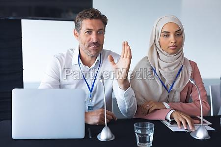 geschaeftsleute sitzen bei konferenztreffen zusammen am