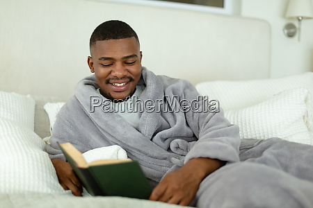 man reading a book while lying