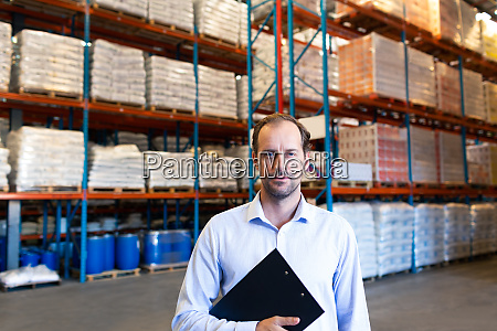 male supervisor holding clipboard and looking