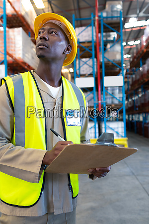 male worker looking away while writing