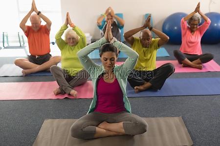 senioren die yoga mit trainerinnen im