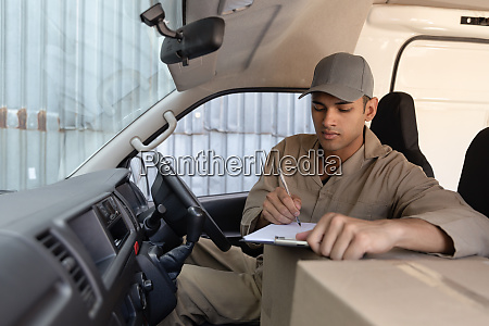 delivery man with cardboard boxes writing