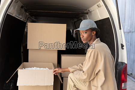 delivery woman unloading cardboard boxes from