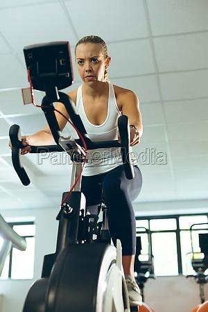 frau trainiert mit heimtrainer im fitnessstudio