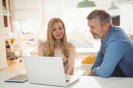 fuehrungskraefte diskutieren ueber laptop im buero