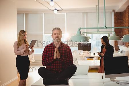 maennliche fuehrungskraft meditiert auf dem tisch