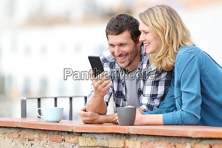 glueckliches erwachsenes paar ueberprueft smartphone auf