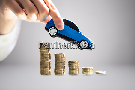 persons hand holding model toy car