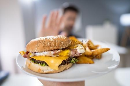 mann lehnt burger von person angeboten