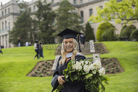 graduating student carrying bouquet at campus