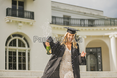 graduating student with opened bottle of