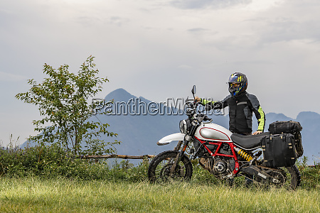 biker posing beside off road motorcycle
