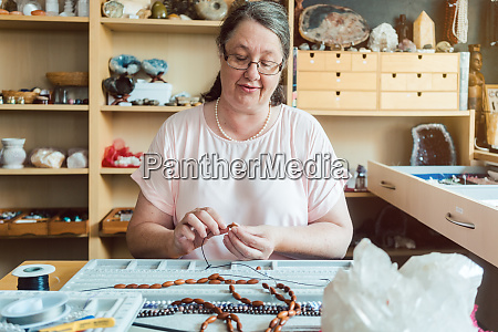 woman working on a gemstone necklace
