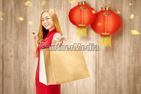 asiatische chinesin in cheongsam kleid haelt