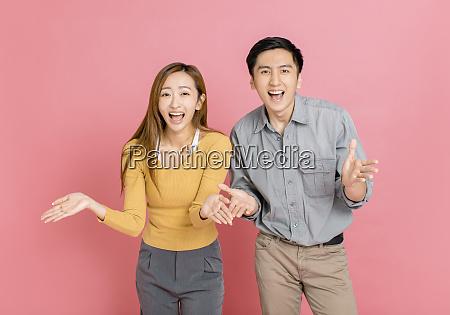 glueckliches junges paar mit armen feiern