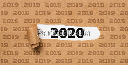 zerrissenes papier enthuellt die zahl 2020