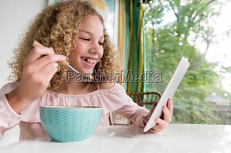 laechelndes maedchen essen fruehstueck mit tablet