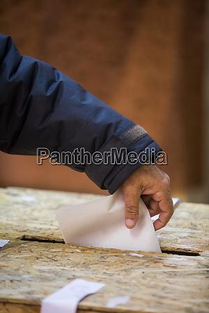 person die waehlt einen stimmzettel abgibt