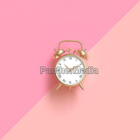klassischer goldfarbener wecker auf zweifarbigem rosa