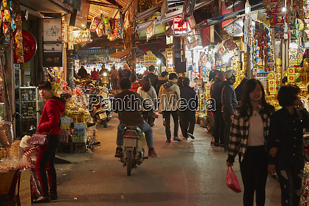 motorcycle and shoppers in night market
