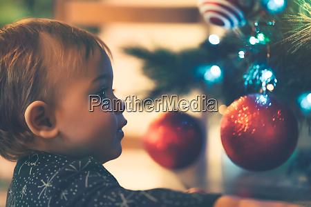 kleiner junge schmueckt weihnachtsbaum