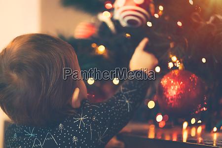 baby junge schmueckt weihnachtsbaum