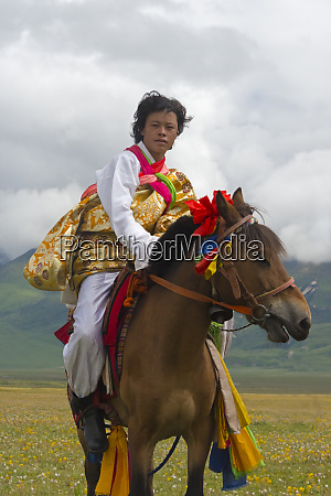 tibetan people in traditional clothing riding