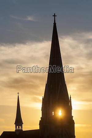 kirchturm gegen einen sonnenuntergangshimmel westlich von