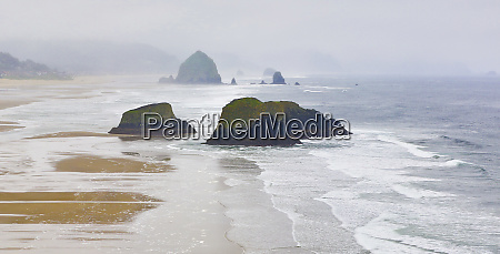 usa oregon cannon beach fog rises