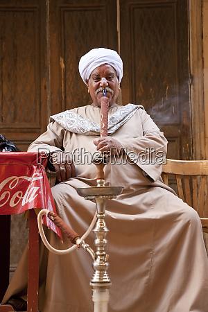 man smoking water pipes or shisha