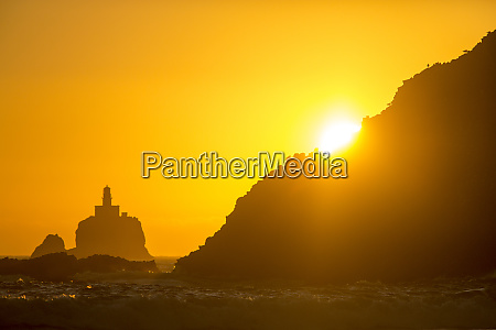 tillamook rock lighthouse silhouetted by setting