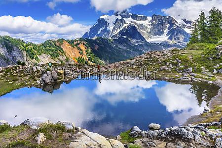 hikers on mount shuksan pool reflection