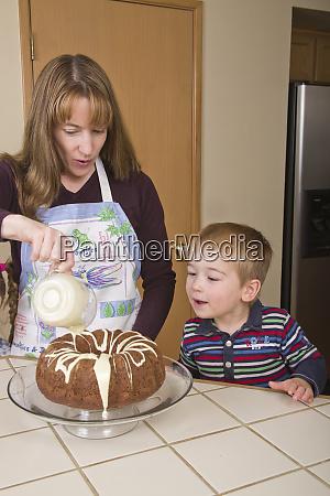 mutter giesst weisse schokoladenglasur auf schokoladenkuchen