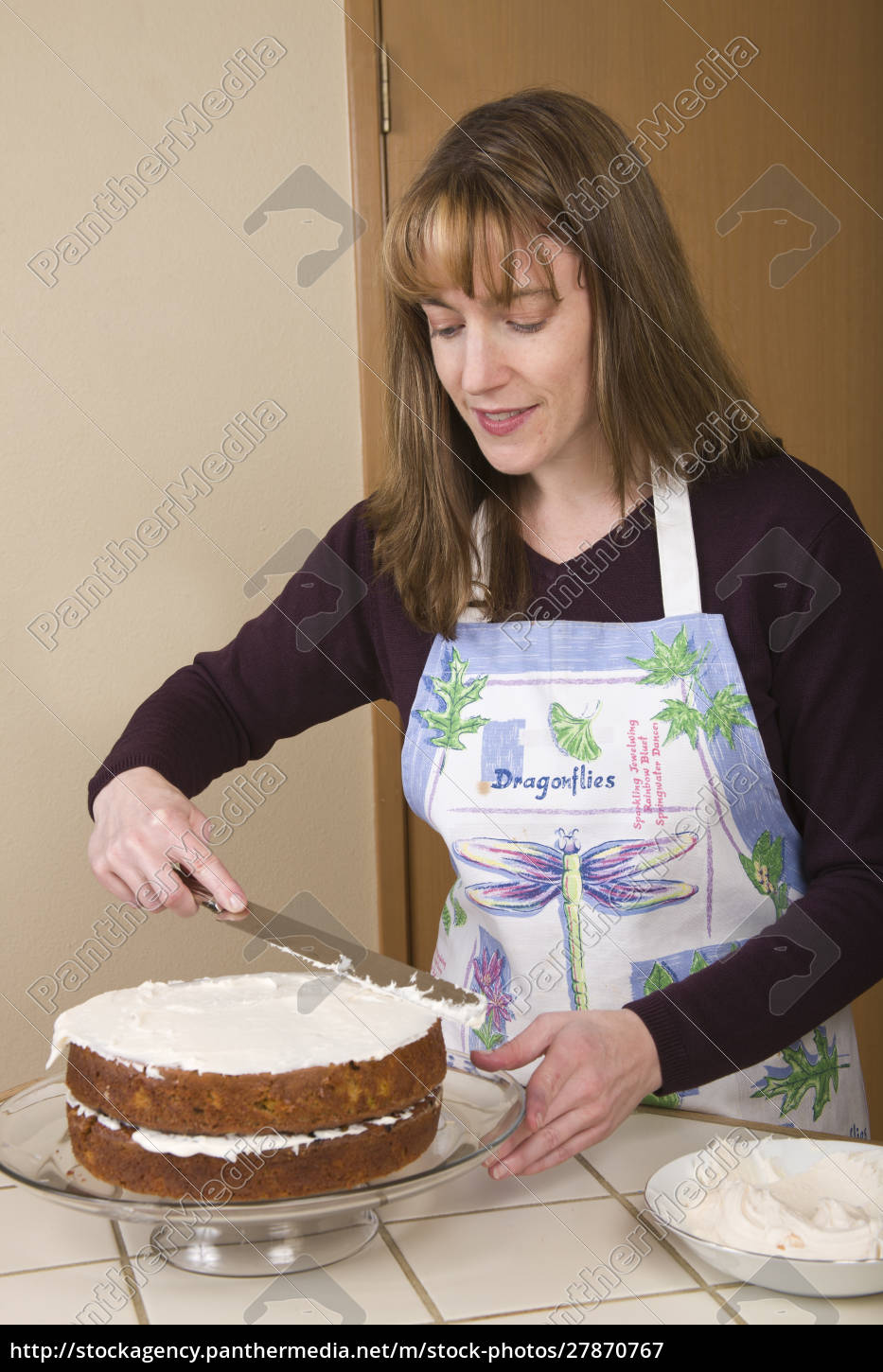 woman, frosting, a, carrot, cake, on - 27870767