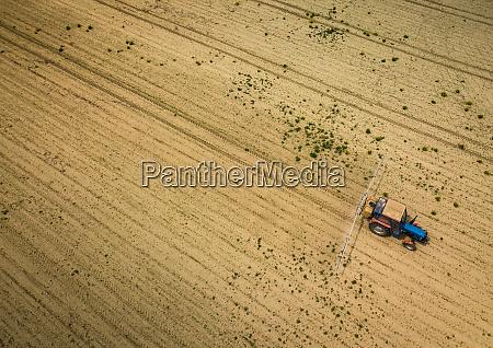 traktor sprueht pflanzen im feld luftaufnahme