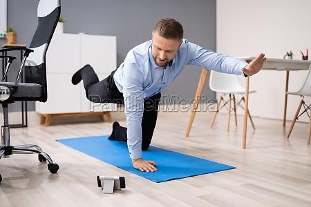 geschaeftsmann macht stretching workout mit smartphone