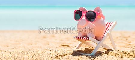 pink piggybank auf deck stuhl ueber
