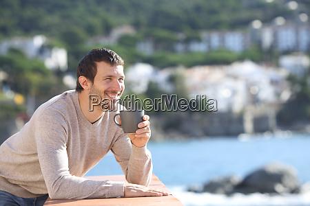 gluecklicher mann trinkt kaffee mit blick