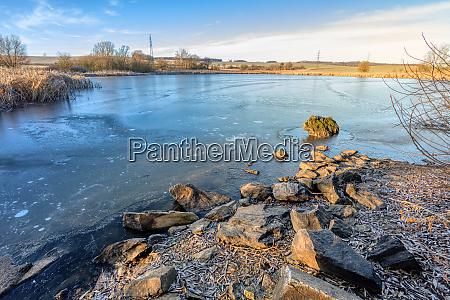 laendliche landschaft mit gefrorenem kleinen teich