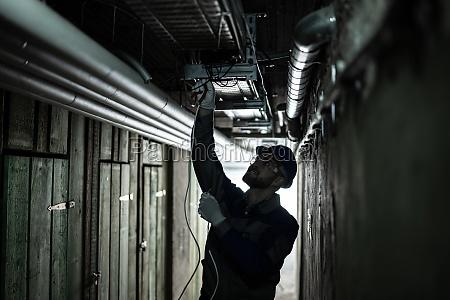 maennlicher elektriker installing light