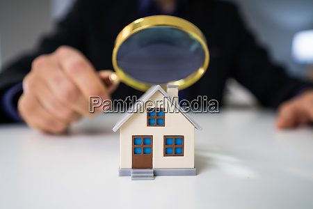 magnifying glass and small house