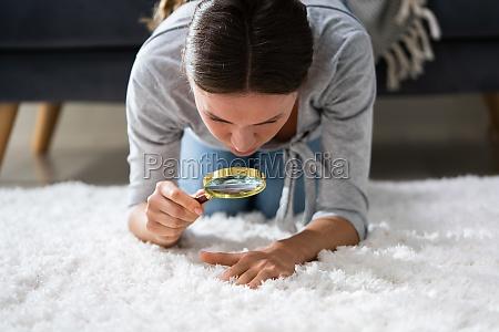 frau blick auf teppich durch lupe
