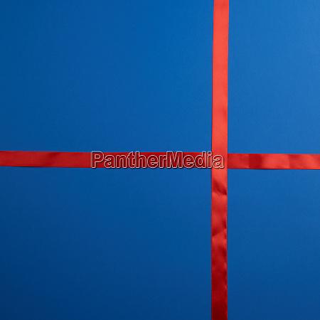 rotes seidenband auf dunkelblauem hintergrund gekreuzt