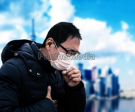asiatischer mann leidet unter husten mit