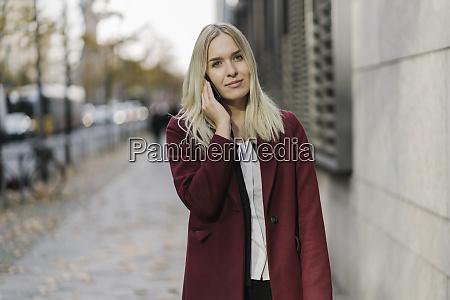 blonde geschaeftsfrau mit smartphone im hintergrund