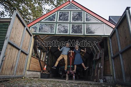 seniorenpaar springt vor bootshaus mit glas